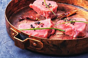 raw steak in frying pan