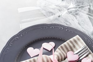 Romantic dinner date plates hearts champagne glasses on gray