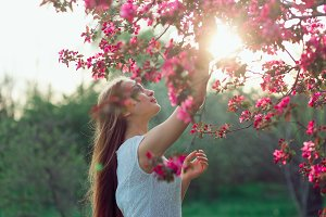Beautiful blonde girl with long hair holding sakura branch among pink cherry blossoms in spring. Evening time