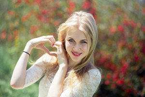 Gesture Love Nature concept - Smiling Young Blonde Woman Showing Heart Shape Made of Fingers over Blossom Spring Background