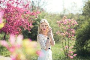 Pretty Blonde Girl Walking in Blooming Spring Sakura Garden