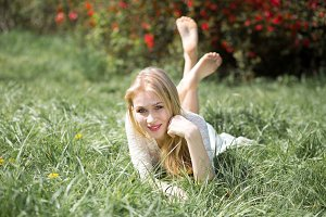 Blonde Young Woman Lying on the Grass with raised legs. Girl lovely smiling and enjoying blossoming in the spring