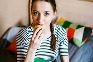 girl lying on the bed and eats Apple