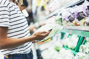 Hipster at grocery using smartphone