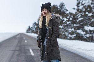 Girl is standing on the winter road