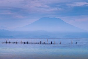 Beautifull evening view to St. Agung Vulcano on Bali from Nusa Penida Island, Net in front some Clouds in Background