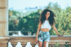 Curly girl near street balcony