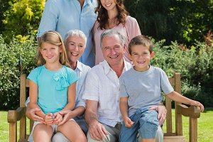Smiling multi generation family sitting on bench in park