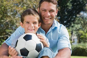 Happy dad and son withfootball in a park