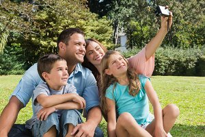 Smiling family in a park taking photos