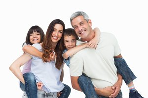 Smiling parents holding their children on backs