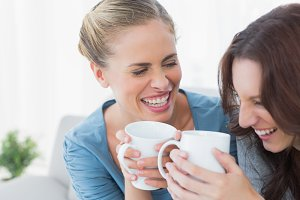 Friends bursting out laughing while having coffee