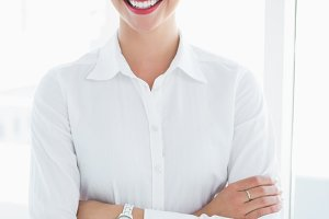 Smiling business woman standing with arms crossed