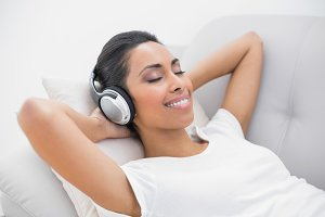 Cute smiling woman lying on couch while listening to music