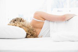 Pretty blonde lying in bed sleeping