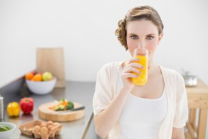 Gorgeous woman drinking a glass of orange juice standing in her kitchen
