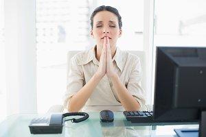 Anxious stylish brunette businesswoman praying