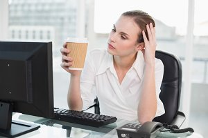 Tired businesswoman holding disposable cup sitting at desk