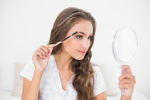 Content attractive brunette using an eyebrow brush and mirror