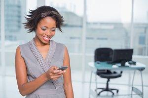 Happy businesswoman standing in her office