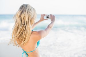 Rear view of attractive blonde in bikini taking a self picture