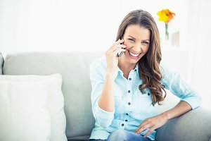 Attractive model sitting on cosy couch having a phone call