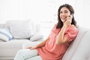 Happy brunette sitting on her sofa on the phone