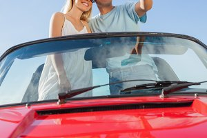 Smiling couple standing in red cabriolet taking picture