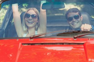 Loving couple having fun in their red cabriolet