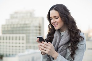 Cheerful pretty brunette in winter clothes sending a text on her smartphone
