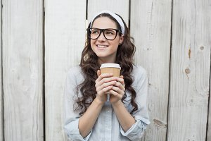 Pensive trendy woman with stylish glasses holding coffee