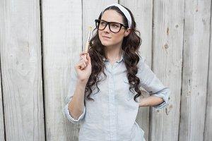Artistic trendy woman with stylish glasses posing holding paintbrush