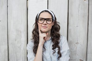 Pensive trendy woman with stylish glasses posing