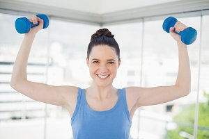 Smiling fit woman exercising with dumbbells