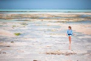 Adorable little girl on the beach in low tide in Zanzibar