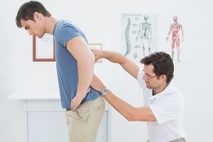 Male physiotherapist examining mans back in office