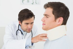 Doctor examining a patients sprained neck