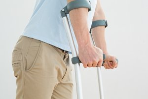 Closeup mid section of a man with crutches