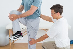 Therapist helping man with stretching exercises in gym hospital