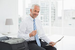 Businessman with coffee cup reading newspaper by luggage