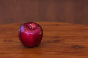 Red apple on wooden table and brown background