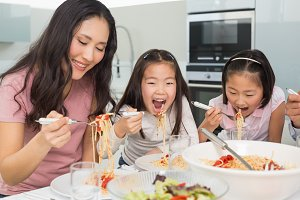 Woman with kids enjoying spaghetti lunch in kitchen