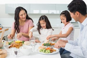 Family of four enjoying healthy meal in kitchen