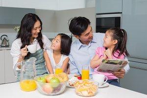 Family of four enjoying healthy breakfast in kitchen
