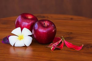 Red apples with flower and leaves on wooden brown table