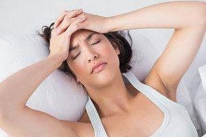 Sleepy woman suffering from headache in bed