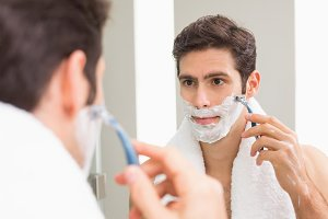 Young man with reflection shaving in the bathroom