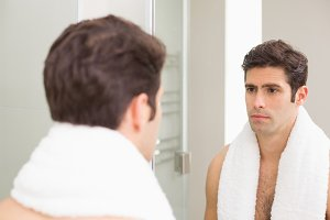 Tensed young man looking at self in bathroom mirror