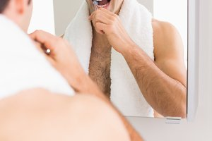 Young shirtless man with reflection brushing teeth
