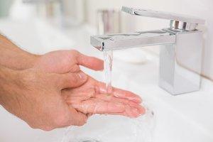 Washing hands under running water at bathroom sink